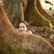 Girl peeping from behind Moreton Fig — Stock Photo