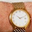 Постер, плакат: Gold watch with white face on hairy wrist