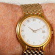 Gold watch with white face on hairy wrist — Stock Photo