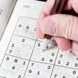 Man hand holding pencil on sudoku puzzle - Stock Photo