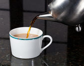 Tea poured from stainless steel teapot — Stock Photo