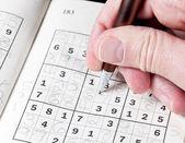Man hand holding pencil on sudoku puzzle — Stock Photo