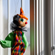 String puppet gazing outside window in sun - Stock Photo