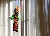 String puppet gazing outside window in sun — Stock Photo