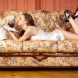 Stock Photo: Pretty womhas relaxed on sofwith small dog.