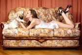 The pretty woman has relaxed on a sofa with a small dog. — Stock Photo