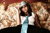 A woman sitting on sofa in a cowboy hat. — Stock Photo