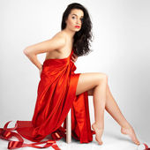 Beautiful young woman is covered with red cloth. — Stock Photo