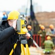 Surveyor works with theodolite - Stock Photo