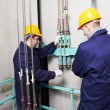 Stock Photo: Machinists adjusting lift in elevator hoistway
