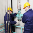 Machinists adjusting lift in elevator hoistway - Stock Photo