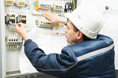 Electrician with drawing at power line box — Stock Photo