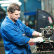 Stock Photo: Auto mechanic at repair work with engine
