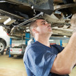 Auto mechanic at car suspension repair work - Stock Photo