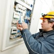 Electrician installing energy saving meter - Stock Photo
