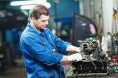 Auto mechanic at repair work with engine — Stock Photo
