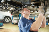 Auto mechanic at car suspension repair work — ストック写真