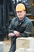 Builder in dirty workwear at construction site — Stock Photo