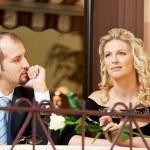 man en meisje met wijn in café op een datum — Stockfoto