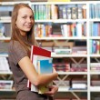 Young student girl with books in library - Stok fotoğraf