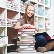 Stock Photo: Smiling young adult womreading book in library