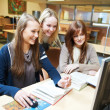 Student girls working with computer in library — Stock Photo