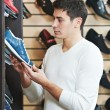 Young man at choosing shoe in clothes store — Foto de Stock