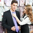 Man and assistant at apparel clothes shopping — Stock Photo