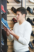 Young man at choosing shoe in clothes store — Stock Photo