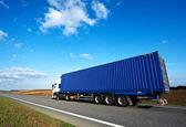 Rode vrachtwagen met grijze aanhangwagen over blauwe hemel — Stockfoto