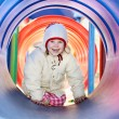 Laughing little baby girl in tube — Stock Photo
