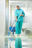 Woman cleaning hospital hall — Stok fotoğraf