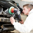 Stock Photo: Mechanic repairing and polishing car headlight