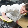 Mechanic repairing and polishing car - Stock Photo