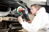 Mechanic repairing and polishing car headlight — Stock Photo