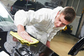Mechanic repairing and polishing car — Stock Photo
