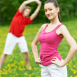 Young man and woman doing stretching exercises — Foto de Stock