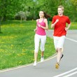 Young man and woman jogging outdoors — Stock Photo #10571548
