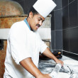 Stock Photo: One chef baker in white uniform juggling with bakery pastry for pizza at kitchen
