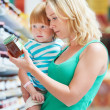 Woman and child choosing produces in grocery shopping mall - Stock Photo