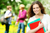 Smiling student girl outdoors with workbooks — Stock Photo