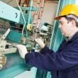 Machinist with spanner adjusting lift mechanism — Stockfoto