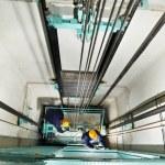Machinists adjusting lift in elevator hoistway — Stock Photo