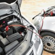 Starting car engine with battery jumper cables - Foto de Stock