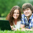 Two smiling young students outdoors with computer — Stock Photo #10672677