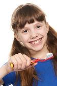 Kleines mädchen mit zahnpasta auf die zahnbürste lächelnd — Stockfoto