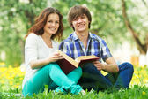 Two smiling young students outdoors with book — Stock Photo