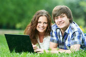 Two smiling young students outdoors with computer — Stock Photo