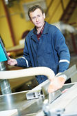 Worker at workshop with circ saw — Stock Photo