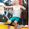 Positive man at chest pectoral exercises machine — Stock Photo #8127702